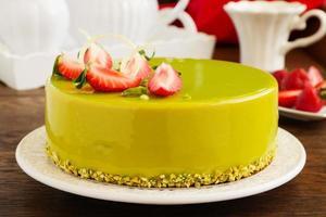 délicieux gâteau mousse à la fraise et à la pistache avec un glaçage lisse.