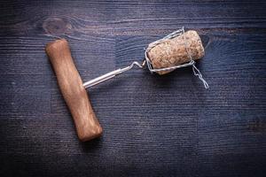 Corckscrew et corck de champagne avec fil sur bois vintage photo