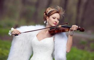 mariée dans une robe de mariée avec un violon. photo