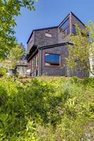 maison moderne en bois noir avec jardin de printemps.