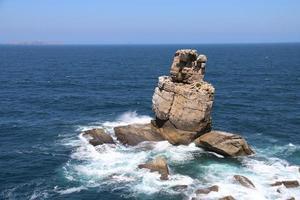 roches côtières dans l'océan bleu photo