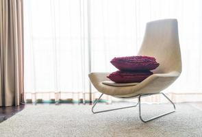 chaise avec oreillers devant une fenêtre