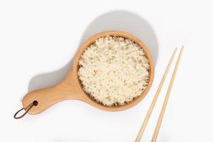 Riz cuit dans une cuillère en bois et des baguettes sur fond blanc