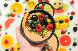 personne tenant un smoothie aux fruits