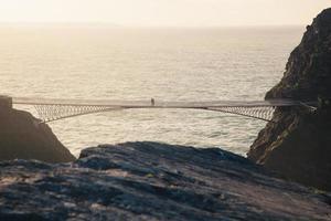 personnes marchant sur un pont à l'heure d'or