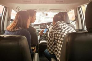 Groupe d'amis regardant la carte en voiture photo