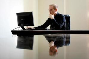homme caucasien blanc assis à l'ordinateur derrière un bureau en verre