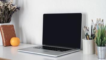 ordinateur portable avec des brosses dans des tasses sur un bureau