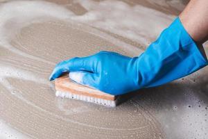 Gros plan d'une personne nettoyant une surface avec une brosse photo
