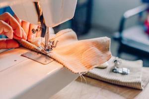 tissu de couture de mains féminines sur machine photo