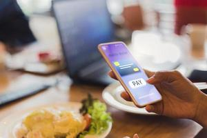femme paie la nourriture en utilisant un téléphone mobile photo