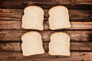 Quatre tranches de pain, sur fond de planches de bois