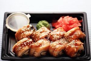 Service de livraison rouleaux de nourriture japonaise dans une boîte en plastique photo