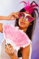 femme avec des masques de carnaval tient un ventilateur