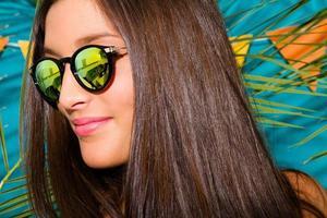 fille avec des lunettes de soleil miroir sur un fond avec feuille de palmier
