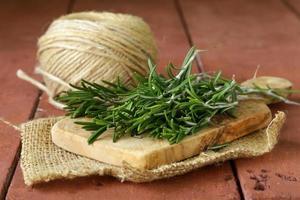 Romarin vert frais sur une planche à découper en bois photo