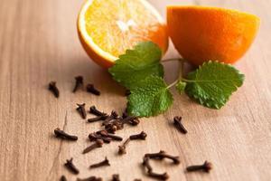Orange, menthe et clous de girofle sur fond de bois photo
