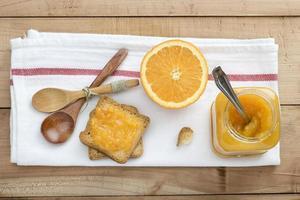 pain grillé et confiture d'orange sur table en bois photo