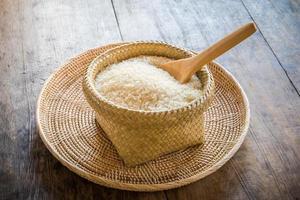 Cuillère en bois dans un panier de riz au jasmin sur bois
