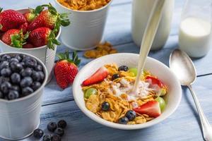verser le lait dans des cornflakes avec des fruits photo