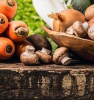 Champignons et légumes sur la vieille table en bois sombre