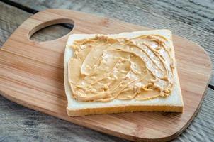 Sandwich au beurre d'arachide sur la planche de bois photo