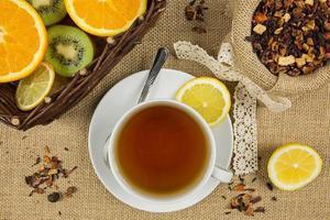 tasse de thé chaud, feuilles d'herbes et fruits mûrs