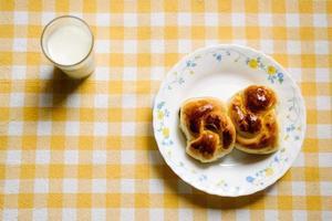 deux petits pains sucrés et un verre de lait chaud photo