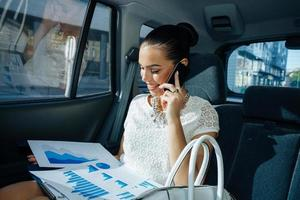 jeune femme d'affaires parlant au téléphone dans la voiture