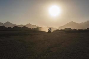 safari hors route dans le désert avec coucher de soleil photo