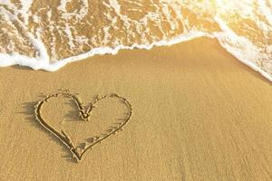 coeur dessiné dans le sable de la plage de la mer, vague douce. photo