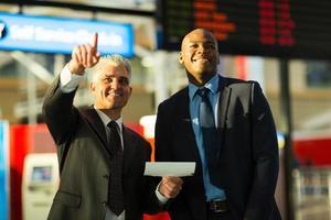 les voyageurs d'affaires pointant sur le panneau d'information de vol photo