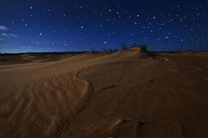 dunes de sable du désert sous un ciel étoilé photo