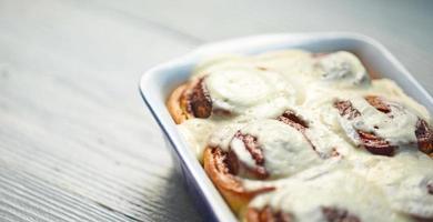 Rouleaux de cannelle dans un plat de cuisson en céramique sur tableau blanc photo