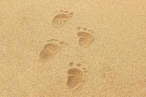 empreintes de pas de bébé dans le sable d'une plage photo