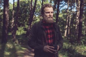 observant barbe homme tenant un appareil photo vintage dans la forêt.