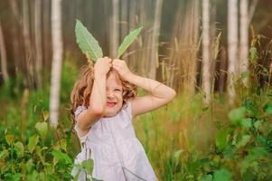 fille enfant jouant avec des feuilles vertes dans la forêt d'été photo