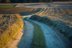 route rurale sablonneuse et champs labourés
