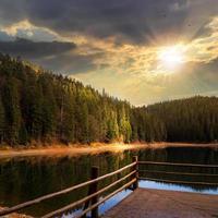forêt de pins et lac près de la montagne au coucher du soleil