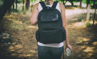 femme avec sac à dos dans la forêt. vue de l'arrière. photo