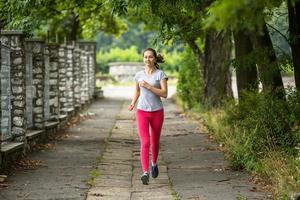 jeune femme qui court sur la piste à travers le parc d'été. photo