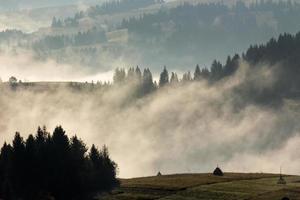 brouillard froid sur le lever du soleil chaud dans les montagnes photo