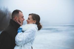 beau couple sur le quai dans le brouillard d'hiver. photo