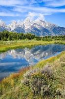 Vue sur les montagnes de Grand Teton avec reflet de l'eau et fleurs photo