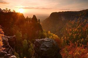 coucher de soleil d'automne dans les rochers. roches au-dessus de la vallée colorée de l'automne