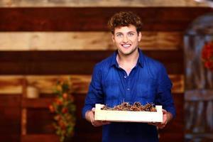 homme tenant une boîte en bois avec des pommes de pin photo