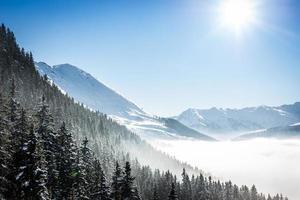 Montagnes d'hiver couvertes de neige avec du brouillard dans la vallée photo