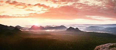 panorama de paysage brumeux rouge dans les montagnes. fantastique lever de soleil de rêve photo