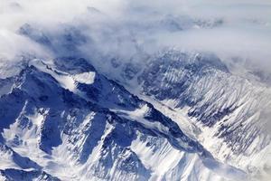 vue de dessus sur les montagnes de neige et glacier dans la brume photo