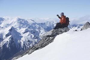 grimpeur prenant une photo de montagnes enneigées